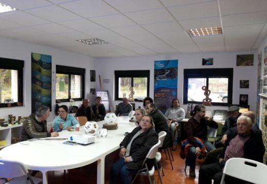 Un grupo de veciños e veciñas participan en Touro na charla sobre a vespa velutina